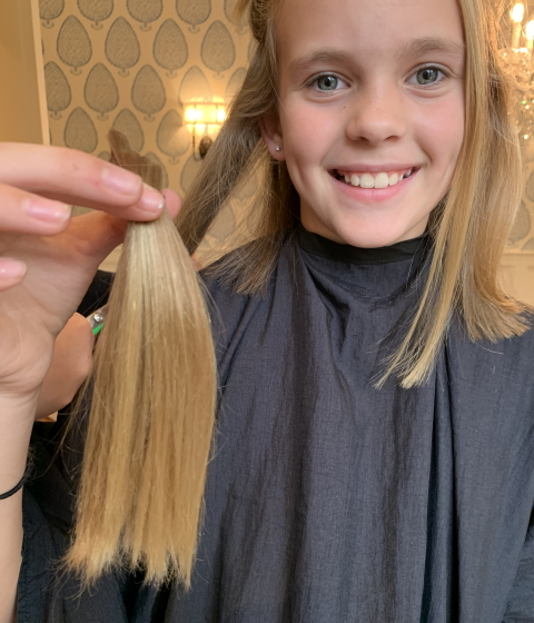 Olivia holding a lock of hair she cut off to donate